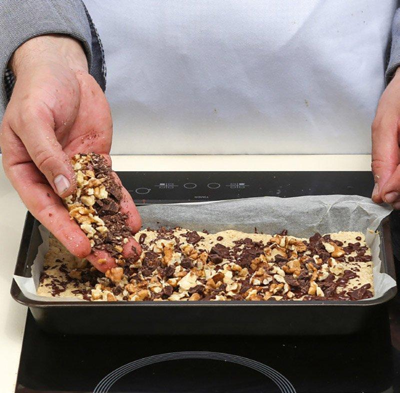 шоколад и грецкие орехи на готовом корже